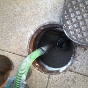 An overhead view of a man cleaning a grease trap